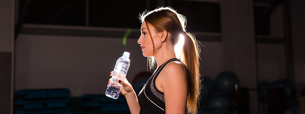 Woman drinking water in a dark gym. Hemp products for pain management.