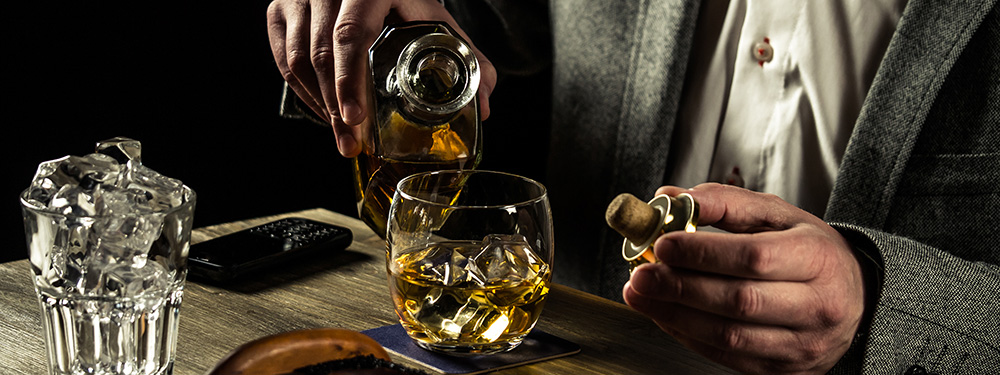 Adult male pouring whisky. CBD oil may help manage issues with anxiety and depression.