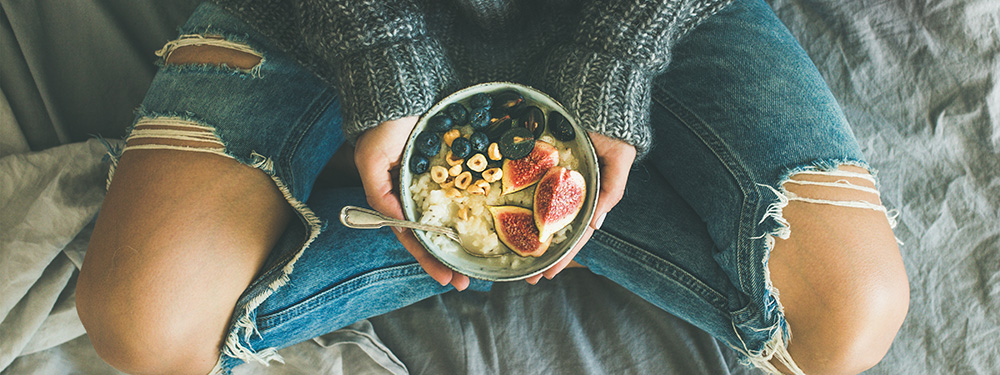 Woman with healthy fruit cereal. Hemp CBD products may help decrease appetite. Buy hemp CBD oil online.