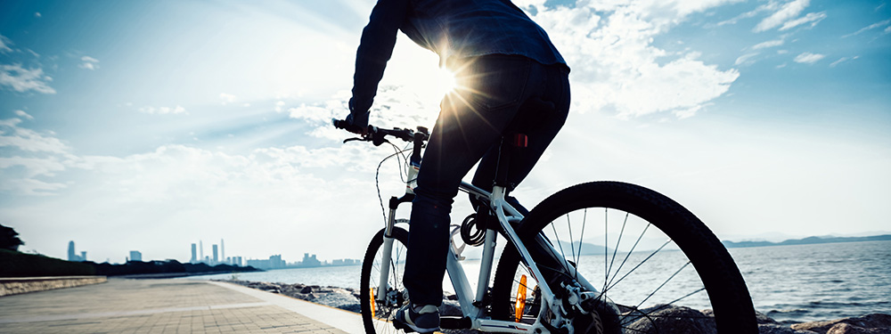 Man cycling in by a lake in the morning after using CBD for weight loss. Buy CBD oil online USA.